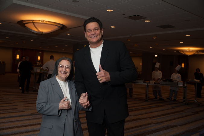 Dan Hampton poses with one of the nuns at the annual fundraiser dinner and silent auction for presence health, event photography by fab photo.